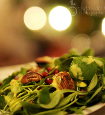 Green Salad garnished with roasted pecans, fresh pomegranate seeds and mango dressing